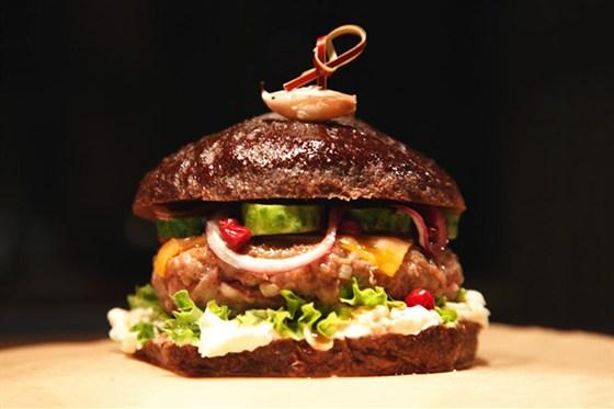 Ресторан Kotleta - фотография 1 - kotlet-burger с соусом из вологодской брусники, бочковым огурцом, печеным чесноком и сырным дипом на бородинской булке