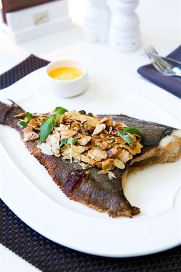 Ресторан Graf-in - фотография 15 - Морская камбала, подается целиком с глазированным миндалем и соусом Холондез