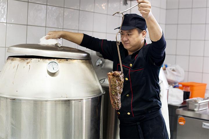Мастер барбекю Питер Сан достает из барбекю-котла приготовленный кусок мяса
